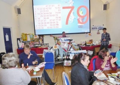 Prizes being shown at Ravensthorpe Village Hall bingo evening.